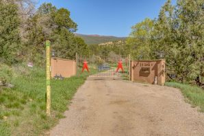 A Rare Find...Stunning Custom Home situated  5+ acres of total peace and quiet in Tijeras w/a flowing creek through the property & ponds. 3,100 sq ft home offers 3 bedrooms in main house, two of which are master suites, a 4th bedroom in separate guest suite/studio. This area boasts a private space with 3/4 bath and living area! Property is equipped with a 2,000 sq ft 4 car garage and an 1800 sq ft barn with 2 horse stalls, chicken coop and plenty of storage plus a fantastic workshop space. So many areas with ultimate privacy, Enjoy porches off of every living area. Amazing, lush yard, surrounded by mature trees, ponds and a stream make for great spaces for entertaining and large functions! Private gated driveway is lined with fruit trees fruit trees including cherry, pear, peach & plum...