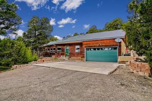 Dynamic one owner, single-story casa, tall ceilings, adorned in a stylish open concept, crafted with many wonderful south facing windows to bring in the light, and savor the amazing views from outside from 3 wooded acres bordering the Cibola Natl. Forest.  Two spacious living areas, or a great area for a formal dining area for family gatherings and entertainment.  Three spacious bedrooms, two gorgeous full baths.  Master Retreat is separated from other bedrooms, with own entrance, steps from the hot tub nestled in the tall forest.  Master Bath is beautiful with separate shower and relaxing soaking tub.  Two secondary bedrooms with plenty of closet room and ideal for a study or guests.  Laundry Room is a nice plus. The 2 car garage is spacious! Tree Top jetliner views* a very special spot!!