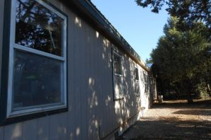 This Palm Haber Home is Secluded On A Fully Fenced 2.39 Acres With Many Beautiful Ponderosa Pines. One Of A Kind Iron Fence With Electric Gate Greets You As You Enter Your Private Paradise. This 4 BR Home Offers A Spacious And Open Floor Plan With 2 Living Areas! The Main Living Room Has APellet Stove And The Family Room Has A Wood Burning Stove To Keep You Warm And Comfortable During The Cold Winters. The Spacious Country Kitchen Offers Plenty of Cabinets. Entertain Your Guests In The Formal Dining Room. The Master Suite Is Separate & Spacious With A Spa-like Bath Which Includes A Jetted Tub & Separate Shower. Property Has A NEW Metal Roof, Water Heater, Bathroom Plumbing, Floors in Bathroom & Laundry Room, Backup System Pump & Pump In Water Tank Shed.