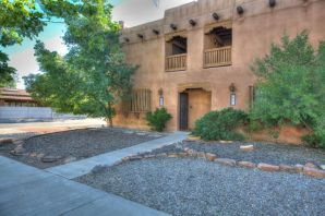 Enjoy Santa Fe style and Albuquerque affordability in this charming, cozy Hap Crawford townhome! Stylish updated baths & lighting, polished brick floors, kiva fireplace, high beamed ceilings with ceiling fans, large private rear courtyard & shaded front balcony, covered & open off-street parking. Energy-efficient quality construction with tons of built-in storage. Great Downtown neighborhood provides convenient location for attorney, therapist, architect, designer or graduate student. No HOA. You will not want to miss this one.