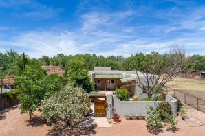 OPEN Sunday 1-3!  Welcome to this lovely, private home in a convenient area of the North Valley. Enter through a custom gate into a beautifully landscaped courtyard.  French doors lead into tile entryway and onto a large living area with hardwood floors, plaster walls and gas log fireplace. Wet bar off the living room with wine cooler.  The kitchen opens to large dining room/living area with banco and french doors opening to a trellised patio with wood burning kiva fireplace. Master bdrm suite with separate office that opens to courtyard, large walk in closet and bath with double sinks and free standing tub! Large pantry and laundry room with built in folding table. Refrigerated air.  Oversized 2 car garage.  The home was completely remodeled in 2005. Back .48 acre lot available separatel