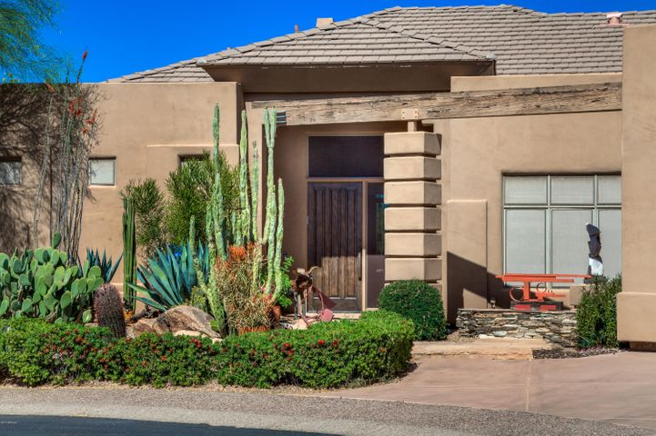 Mature and beautiful landscaping surround the entrance of the home.