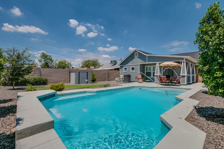 Luxury backyard with covered patio, extended decking, storage shed, 2 RV Gates, and NEW sparkling Quartz pool with new plaster, water features, and LED color changing pool light.