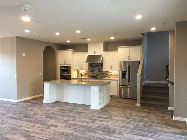 Chefs kitchen with staggered white maple cabinets and quartz tops