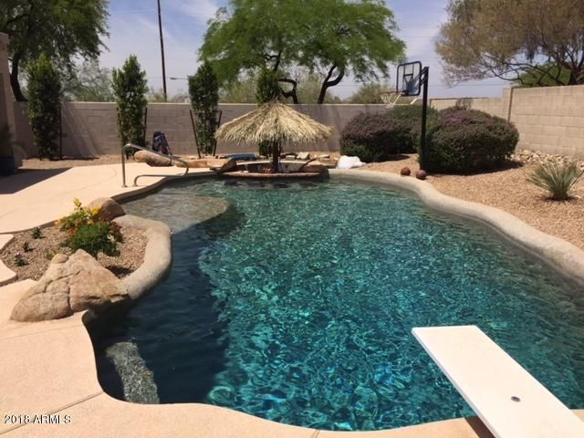 Pebble-tec diving pool includes shallow seating area with swim up tiled seating at flagstone bar.