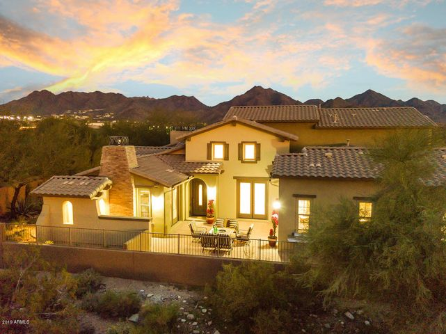 This home is surrounded by beautiful mountain views and natural desert landscaping.