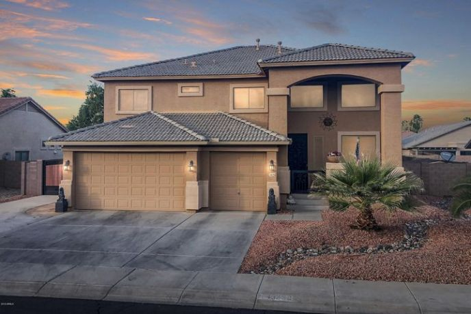 Front of house with 3 car garage, RV gate and low maintenance desert landscaping