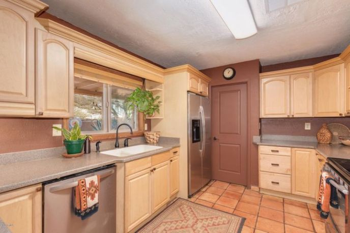 Kitchen sink has window overlooking pool & horses.