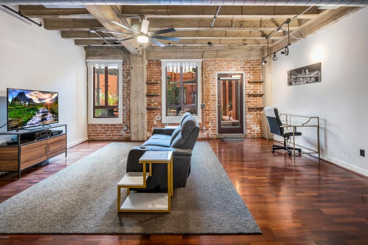The main living space has direct patio access, hardwood floors and exposed brick.
