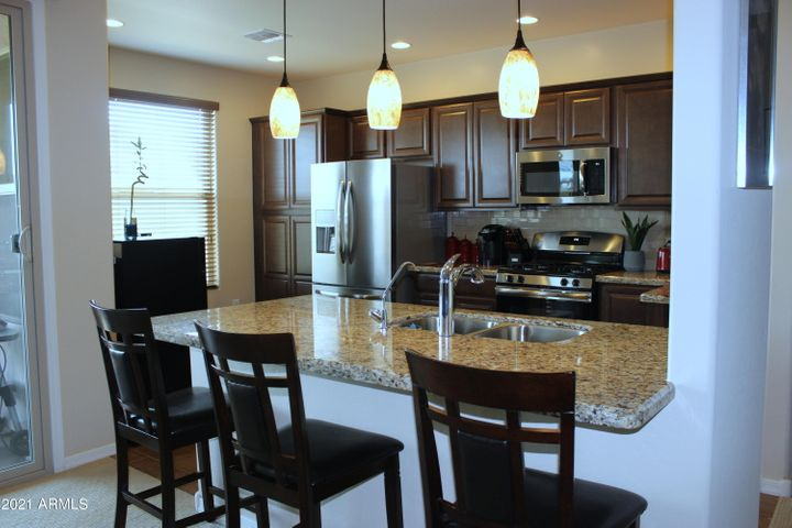 Tall windows, pendant lights, gas stove, granite counters - a Chef's Dream!