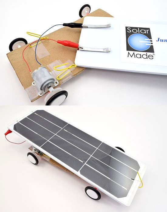 Two alligator clips from a motor connect to the back of a solar panel