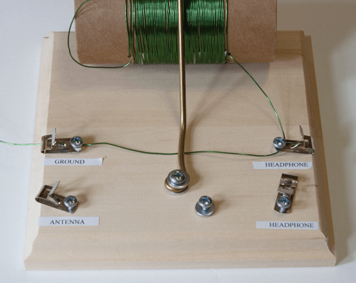 Wire from a homemade crystal radio tuning coil connects to ground and headphone clips