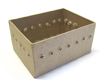 Evenly spaced holes are drilled at an even height around a paper mache box