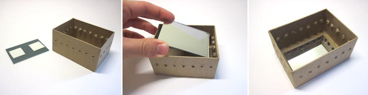 A mirror is placed at the bottom of a box and secured inside with double-sided tape