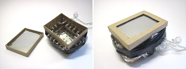 A lid with a plexiglass mirror is placed onto a box with a mirror and LEDs