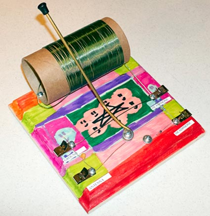 The wooden base of a homemade crystal radio decorated with paint