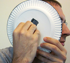 A person holding a paper plate to their ear