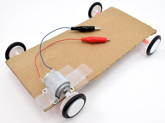 A motor is aligned with the gears on the axle of a solar powered car and secured with tape