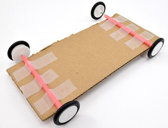 Two axles are taped to a rectangular piece of cardboard which will serve as the chassis for a solar powered car