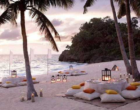 Puffs espalhados ao redor de mesas em casamento na praia. Imagem Pinterest via Estilo Consultorias