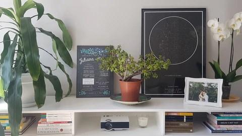 imagem do quadro do Mapa do Meu Céu apoiado em mesa de escritório ao lado de plantas e outros itens pessoais