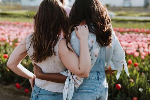 amigas de costas abraçadas olhando campo de flor