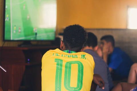 imagem de homem com a camisa do brasil assistindo jogo de futebol