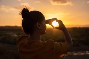 imagem de uma menina fazendo coração com as mãos