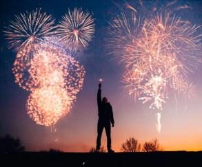 imagem de um homem com o braço levantando no meios dos fogos de reveillon