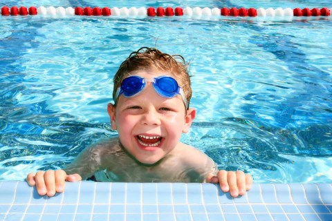 A young smiling boy is at the edge of a swimming pool, with goggles on his forehead.