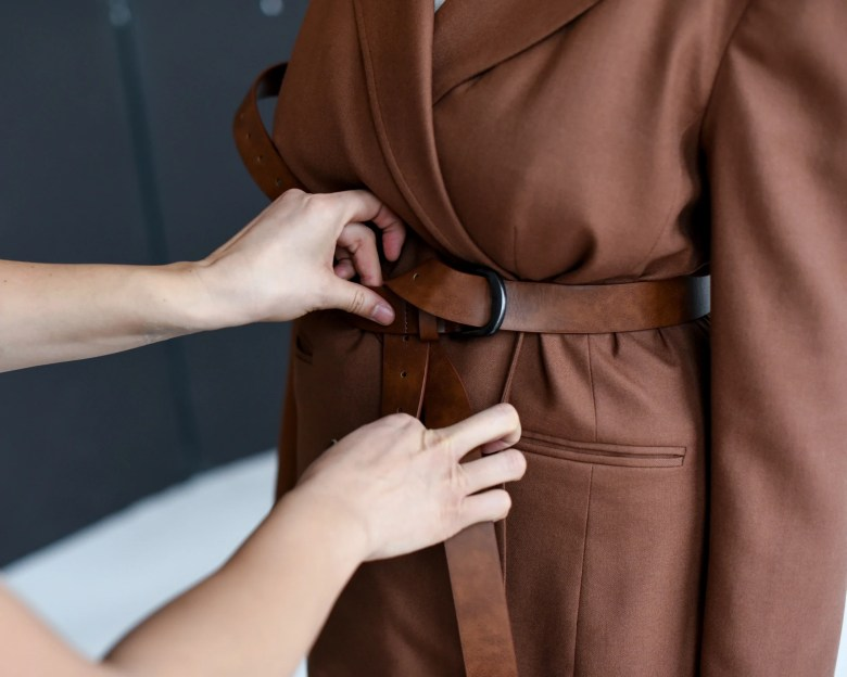Hands adjust the belt of a brown trench coat