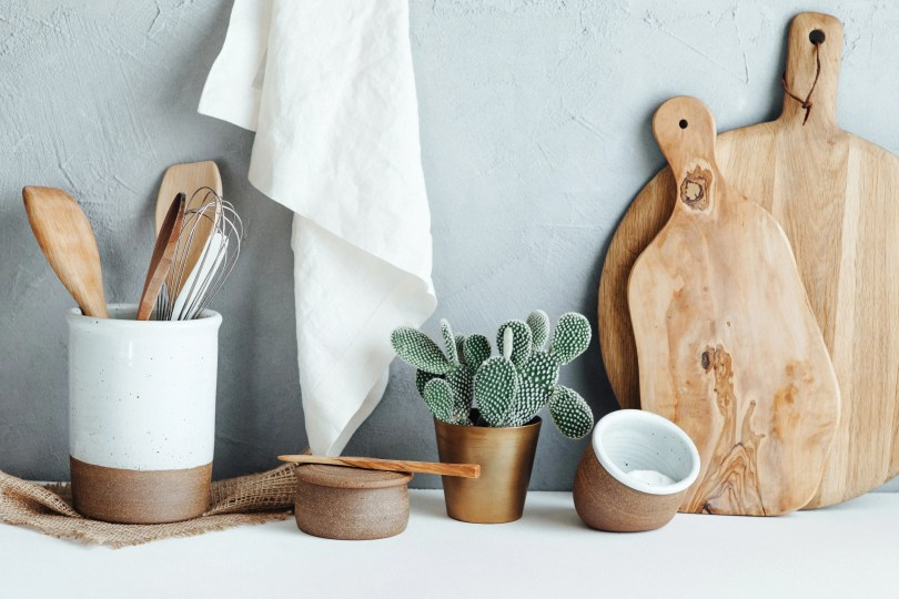 Still life photograph of kitchen products against a pale blue background. Rustic wood cutting boards, small ceramic salt and pepper vessels and a ceramic container for utensils.