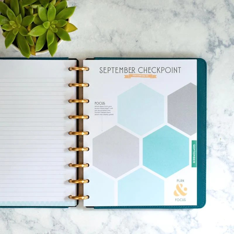 Inkwell Goal Setting Planner lies open on a marble table