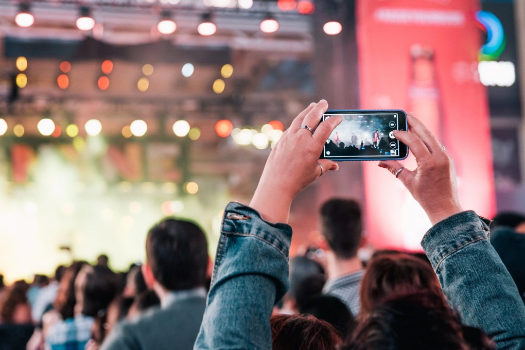 Photo of a concert and a crowd holding mobile phones in the air