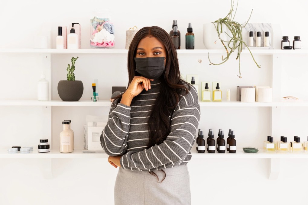 Skincare line founder stands in front of a retail beauty display