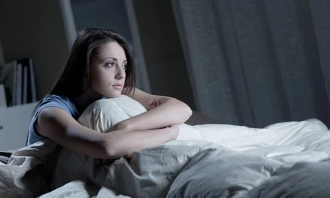 A young woman sitting in bed looking into the distance looking depressed, cradling her legs.
