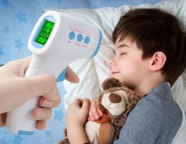 criança cpm termometro apontado para sua cabeça aferindo sua temperatura