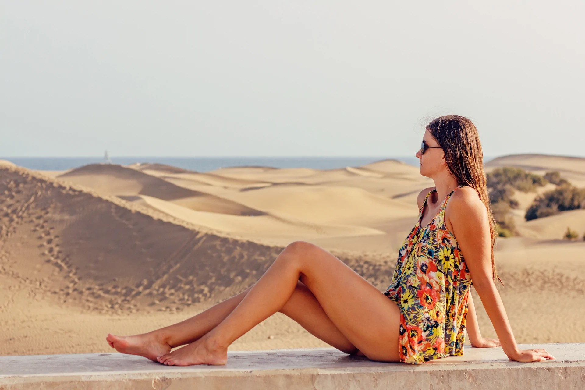 Canva_-_Woman_Sitting_on_Sand_at_Beach_Against_Sky