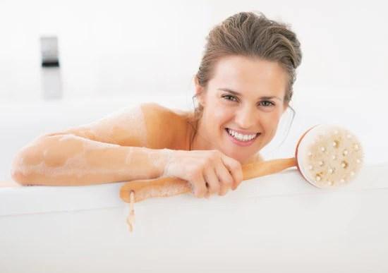 woman on a white bath tub holding a body brush