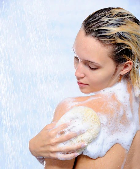 woman taking a bath scrubbing her back left side with a sponge