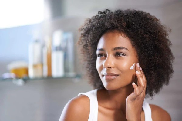 black woman applying cream on her left cheek with middle finger