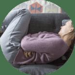 Woman in fetal position on sofa