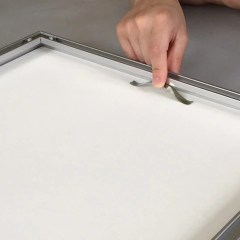 Slide your springs, evenly spaced, into the gap along the edges on the back of the frame