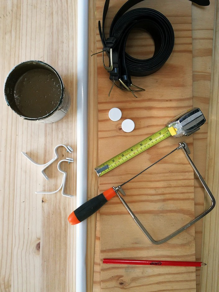 diy hanging shelf materials, including jigsaw, belts, measuring tape, pencil, curtain brackets and plywood