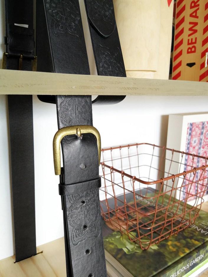 close up of black belt of home made hanging shelf