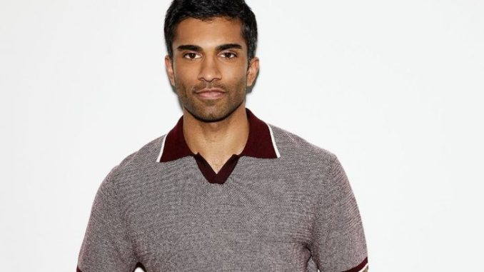 Dashing Nikesh Patel in a faded greyish t-shirt with dark red neck color.