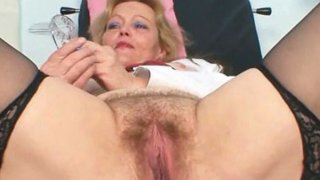 Filthy mature lady toys her hairy pussy with speculum image