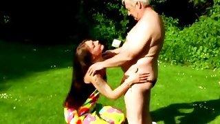 Gorgeous brunette teen blows her older lover's stiff rod in open air image