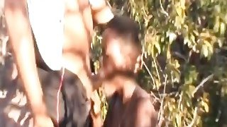 Busty_African_Slave_Forced_To_Suck_Cock_Outdoors image