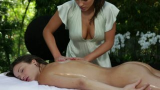 Curvy brunette masseuse rubs and strokes her sexy client's body image